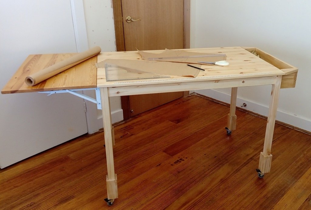 fabric cutting table with tool well and fold down extension